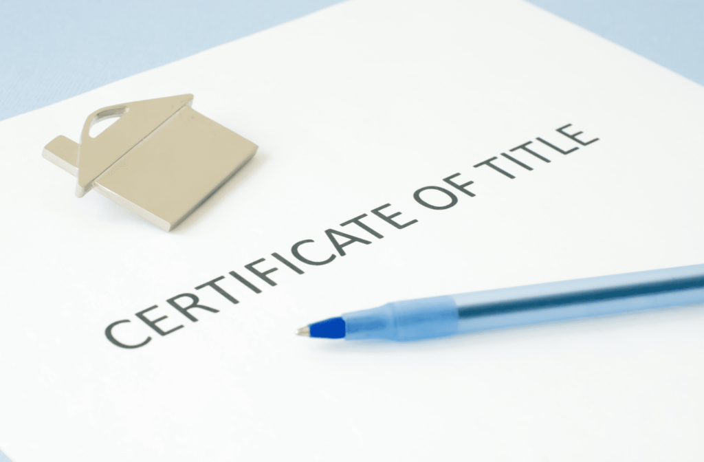 A certificate of title with a pen on top
